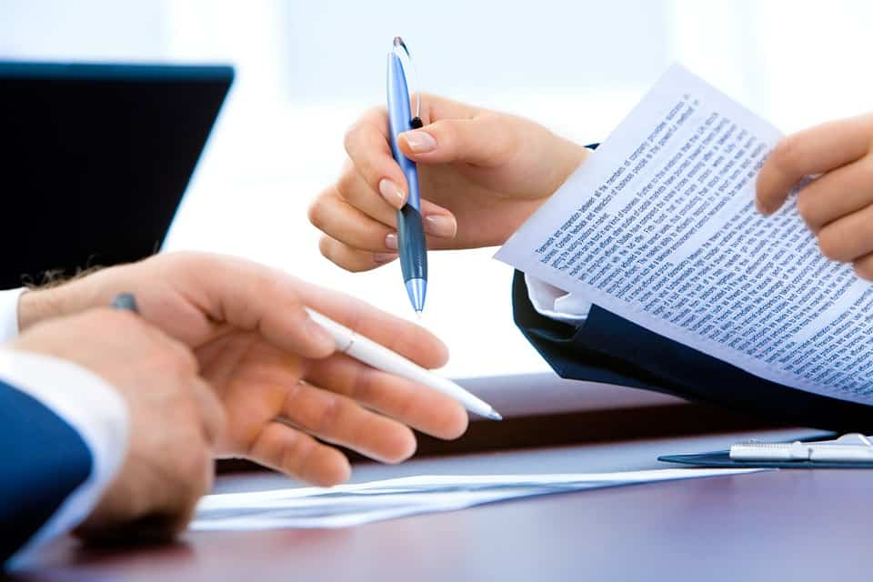 two persons holding pens and paper