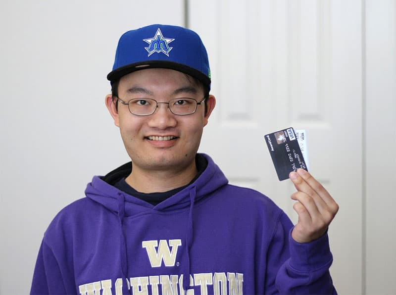 student holding an atm card to get his loan