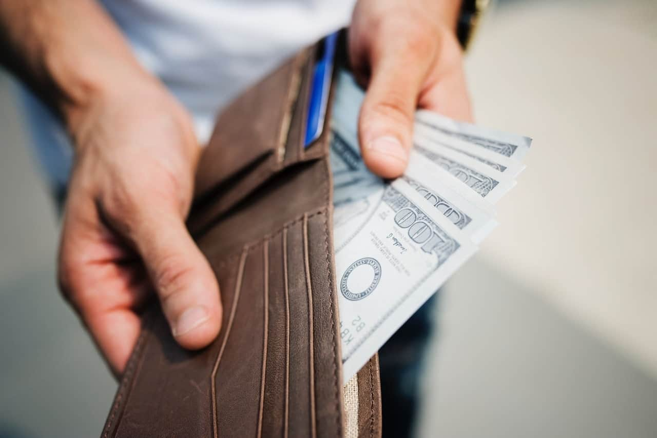 person holding brown wallet with cash