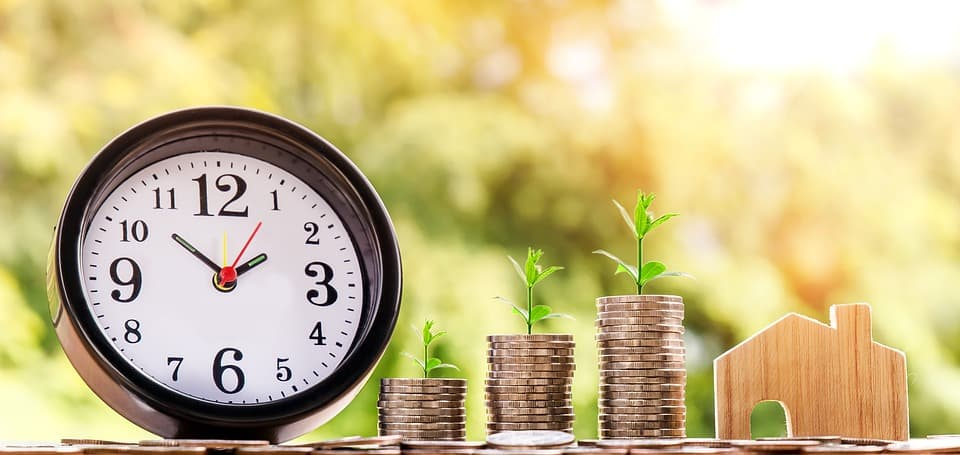 clock beside coins and home-shaped piece of wood